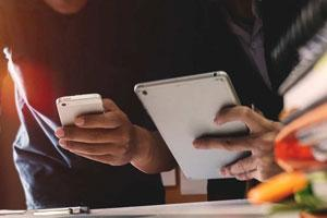 A person uses a smartphone while another person uses a tablet.